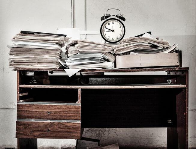 Desk Stacked With Paper Clutter